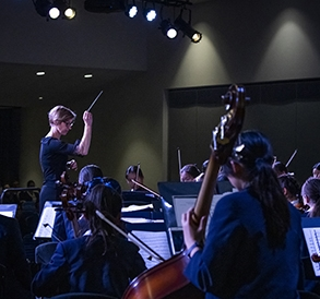 Ms Spooner-Ryan conducting Meriden's musicians at a performance in 2019